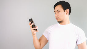 Looking at smartphone. An asian man with white t-shirt and grey background royalty free stock image