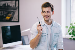 Looking from the smiling men in the office. Stylish designer at work. Worker got idea stock image