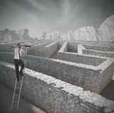 Looking for the solution to the maze. Businessman looking for the solution to the maze Royalty Free Stock Photography