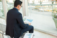 Looking at some charts. Young businessman sitting on a bench while looking at some performance charts at work Royalty Free Stock Photos