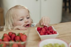 Looking for Some Fruit. High angle view of a little girl raching over the top of a kicthen counter to grab some raspberries. She is looking for something to eat royalty free stock image