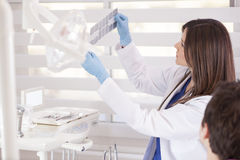 Looking at some x-rays. Female dentist reviewing the x-rays of a patient Royalty Free Stock Images