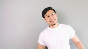 Looking at someone or something up above. An asian man with white t-shirt and grey background stock photo
