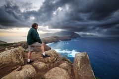 Looking at the storm Madeira. Tourist on the cliffs in the beautiful landscape of the east coast of the island Madeira at Ponta de Sao Lourenco nature reserve royalty free stock images