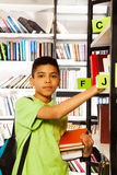 Looking straight boy searches book on shelf. Serious guy looks straight and searches book on bookshelf in school library Royalty Free Stock Images