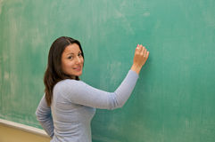 Looking Student writing on blackboard Stock Images