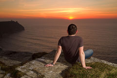 Looking for a sunset. Man at relaxation on Cliffs of Moher at sunset Stock Image
