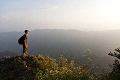 Looking into the Sunset. A hiker takes a momant to enjoy the sun set atop Chicken Foot Mountain in Yunnan province, China Royalty Free Stock Photos