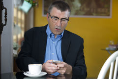 Looking surprised  while texting on his cellphone Royalty Free Stock Photos