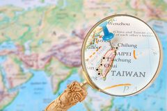 Looking in on Taipei, Taiwan. Blue tack on map of the world with magnifying glass looking in on Taipei, Taiwan stock image