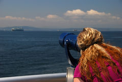 Looking Through Telescope. A woman looks at a boat through a pay-per-view telescope on Seattle's pier Stock Photography