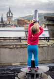 Looking through the telescope. Little girl stretching to to be able to look through the telescope on the viewing platform on top of Camera Obscura in Edinburgh Royalty Free Stock Photography