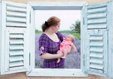 Looking Through The Window To The Young Woman With Her Baby In Her Arms Stock Image