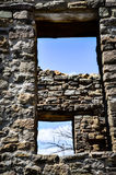 Looking Thru Ancient Windows at A Blue Sky with Bare Branches and Clouds Stock Images
