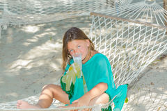 Looking tired little girl sitting in hammock Royalty Free Stock Photos
