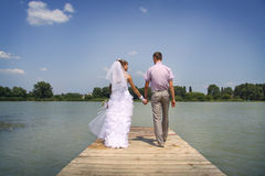 Looking to each other. Young happy newlyweds walking and posing on a riverside Stock Photos