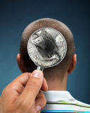 Looking to a head. Looking to a mans head thinking about money through magnifying glass stock photos
