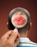 Looking to a head. Looking to a mans head thinking about women through magnifying glass royalty free stock photos