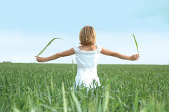 Looking to the Heavens. Small girl standing with her back to the camera looking off into a blue sky. Girl holding out green leafs in her hands as she looks to Royalty Free Stock Image
