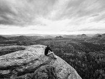 Looking to horizon. Man sit on rock above dense forests or jungle and enjoy view. Looking to horizon. Man sitting on a rock above the dense forests or jungles stock image