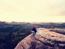 Looking to horizon. Man sit on rock above dense forests or jungle and enjoy view. Looking to horizon. Man sitting on a rock above the dense forests or jungles royalty free stock images