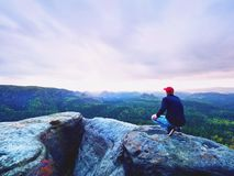 Looking to horizon. Man sit on rock above dense forests or jungle and enjoy view. Looking to horizon. Man sitting on a rock above the dense forests or jungles stock photo
