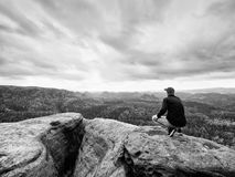 Looking to horizon. Man sit on rock above dense forests or jungle and enjoy view. Looking to horizon. Man sitting on a rock above the dense forests or jungles stock photos