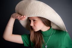 Young pretty girl with big straw hat is looking af Stock Photography