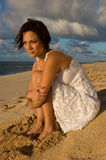 Looking to the sea. Sexy girl sitting on the beach in a white dress (high contrast Royalty Free Stock Images