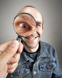 Looking to smiling man with angry eye. Looking to funny smiling man with angry eye through magnifying lens Stock Photos