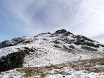 Looking to walkers on a snow-capped Arnison Crag, Lake District Stock Images