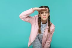 Looking too far. portrait of beautiful cute girl standing with m. Akeup and brown pigtail hairstyle in striped light blue shirt pink jacket. indoor, studio shot stock images