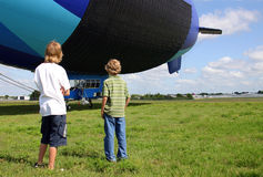 Looking Toward Their Future. Two young teenage boys studying an airship as it swings on its tether Royalty Free Stock Photo