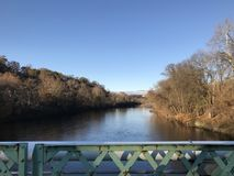 Lehigh River near Easton Pennsylvania, USA as seen from the center of a bridge. Looking toward the town of Easton on an old metal bridge, one can see the Royalty Free Stock Photo
