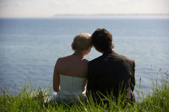 Looking towards the future. Wedding couple looking out over the ocean Royalty Free Stock Photography