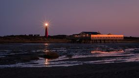 Looking towards the Schiermonnikoog lighthouse from the beach after sundown Stock Photo