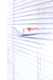 Looking trough blinds. Royalty Free Stock Photos