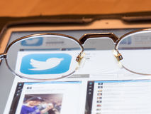 Looking at Twitter. Glasses on a tablet computer framing the Twitter logo for your concepts stock photo