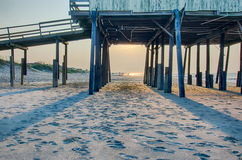 Looking under pier towards sandy beach at avon north carolina. Looking under pier towards  sandy beach Royalty Free Stock Image