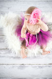 Looking up. Cute baby girl with pearls and tutu skirt - studio shot Stock Photos