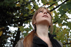 Looking up. Young woman looking up into the trees Royalty Free Stock Images