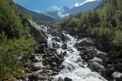 Water from Bionnassay glacier tumbles toward foreground, French Alps. Looking up the Bionnassay creek to the mountain and glacier of the same name. Image taken stock photography