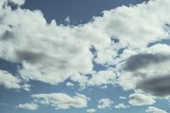 Looking up at a blue overcast summer sky with fluffy, soft white clouds - Concept of daydreaming, weather or meteorology.  royalty free stock photos