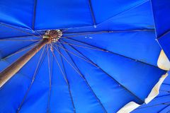 Looking up at a blue parasol. royalty free stock photos
