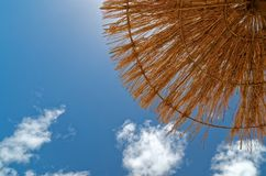 Looking up on the blue sky and straw parasol. Looking up at the straw parasol and the blue sky. This scene was taken on the sandy beach on Sal in Cape Verde stock photography