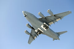 Military Transport Plane. Looking up at the bottom of a large jet transport plane taking off stock photography
