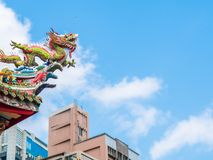 Looking up dragon sculpture on top of chinese temple roof against the blue sky and clouds with copy space. Temple in the city royalty free stock photos