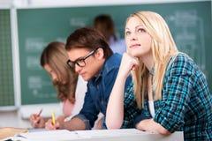 Looking Up While för kvinnlig student sammanträde med klasskompisar på skrivbordet fotografering för bildbyråer