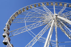 Ferris wheel perspective against blue sky stock photo