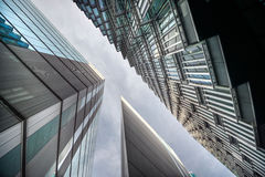 Looking up at futuristic glass covered corporate buildings Stock Photo